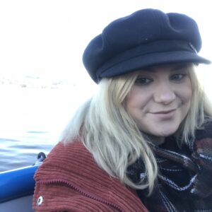 The profile of a smiling face, with a black cap, long blonde hair and a the collar of a red coat.