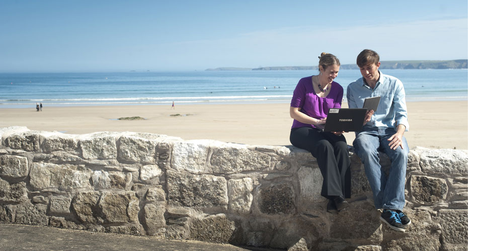 Man and woman sitting on a stone wall in front of a sandy beach. They are looking at a laptop.